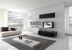 Perfect and Modern Home Interior Design : Modern Home Interior Design In Living Room With Low White Table On Gray Furry Rug As Well Beige Sofa And Floating Cabinet Shelves Above Tv And White Curtain Glass Window