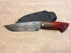 """Made from 1/8"""" thick 1095 carbon steel and has a blade length of about 5 1/2"""" with an OAL of 10"""". It has been professionally heat treated to a RC of 59-61 and been double acid etched. This has Padauk and IPE scales on black G10 liners with copper pin and lanyard hole.It comes with a black kydex sheath made to accept a Blade Tech TekLok which is not included."""