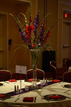 I loved designing this tall arrangement of red and purple gladiolas with curly willow in a trumpet vase. This was a HUGE wedding and a HUGE success. Click on the picture for the story and full reception pics.