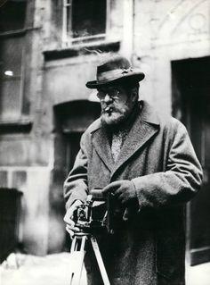 """Mit Kamera und Zigarre: """"Dem arbeitenden Menschen in seinem Kampf zu helfen, danach habe ich immer gestrebt."""" Heinrich Zille mit seiner Kamera."""