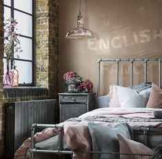 Warehouse Home soft industrial bedroom in pink and grey with vintage industrial furniture and bespoke galvanised steel piping bed