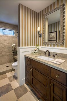 This small bathroom features wallpaper with alternating light and dark neutral stripes, an attractive mirror with scalloped edge, an open tiled shower and a checkerboard floor pattern.