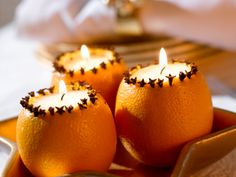 Fill oranges with a candle and accent with cloves for a festive table centerpiece.