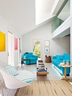シンプルな内装にカラフルな色使いの家具を配した吹き抜けのあるリビング