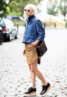 Linhas retas no casaco e na bolsa. Materiais duros e lustrosos.