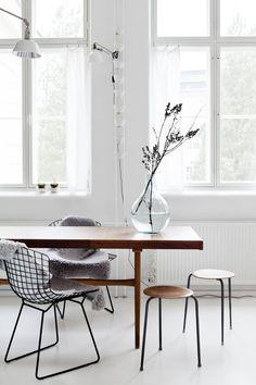 Taljat antavat kotoisaa ilmettä Bertoian klassikko-tuoleille. Niiden parina ovat kirpputorilta hankitut vanhat jakkarat. Ruoka-pöydällä on Annon Väre-kierrätyslasipullo.