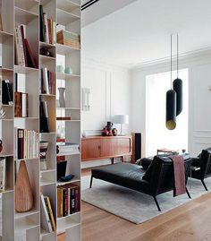 Simple modern living room interior with white shelves, white wall and black sofas