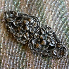 Pewter Arts and Crafts Hand-hammered Wild Roses Buckle. A beautifully crafted belt-buckle in solid pewter, with a lovely plaited edge and hand-hammered wild trailing roses detail. An unmarked piece that is