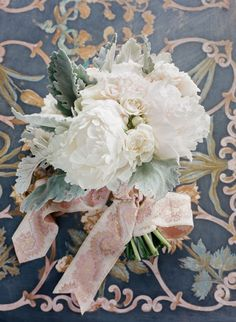 White peonies, roses, lilyof the valley, and lambs earwere tied together with an elegant pink ribbon.