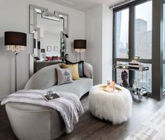 A sleek gray chaise is styled with a fur throw blanket and playful throw pillows in this living room design | Décor Aid