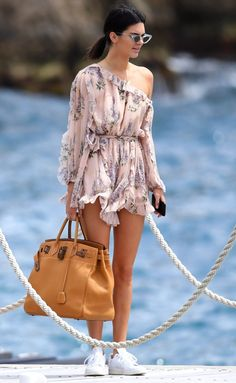 Kendall Jenner in a one-shoulder Zimmerman romper and white sneakers - click through to see more summer outfit ideas
