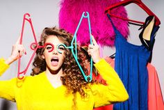 Sensual young girl with curly hair in yellow sweater holding hangers standing amid colorful clothes pink red blue colors on grey wall background, horizontal picture My Life Style, My Style, Colors For Skin Tone, Blue Colors, Skincare Blog, Yellow Sweater, Colourful Outfits, Colorful Clothes, Red And Blue