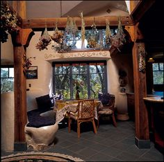 Straw Bale Home in Northern California ~ Dried flowers hang from recycled timber in the dining room.