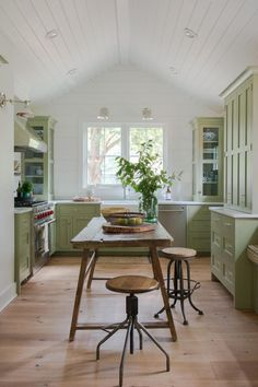 HGTV features a modern cottage kitchen with pea green shaker style cabinets, rustic wood table as an island, industrial counter stools, and a whitewashed vaulted wood ceiling.