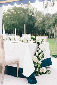 Floral garland on wedding dinner table by Tara Guerard; photo by Corbin Gurkin