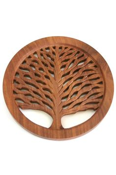 "This stunning wooden tree of life trivet, intricately handcarved with shesham wood, will decorate and protect your table. The purchase of this ethically handmade trivet employs fair trade artisans working with Asha Handicrafts, which in Sanskrit means 'hope,"" a non-profit organization that was started in 1975. Please note that due to the handmade nature of fair trade items, slight variations are to be expected and add to the charm and authenticity.    Measures Approx. 7.5""   Wooden Trivet by…"