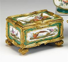 Sevres gilt bronze mounted jewel casket<z> <br  />  <br  /> circa 1760<z> <br  />  <br  /> The side panels painted with exotic birds in rectangular reserves against an apple green ground, the cover depicting an amorous couple with a dog and sheep reclining in a landscape, with finely chased bronze dore mounts, raised on toupie feet. <br  />  <br  /> H: 4 1/4, L: 6 3/4, D: 5 in. <br  />  <br  />