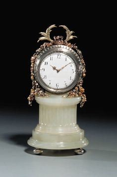 A three-color gold-mounted silver and bowenite Table-clock  marked Fabergé, workmaster Michael Perchin, St. Petersburg, circa 1890, with scrathed inventory number 53177 The circular hardstone pedastal on three gadrooned feet, on stepped base and partly facetted stem, the circular silver mount with tied reed bezel with Greek key-pattern bands, the enamel clock face with Roman chapter and gold hands, marked on reverse.