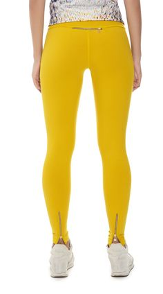 Hey Jo, Cassini Legging, Yellow, Bright .  These bright yellow leggings look great for a workout and perform well with their breathable technology. Leggings have a practical back pocket to hold keys, phone and money. Waist is adjustable with drawstring and gold zippers on ankle for versatile styling. Made in the UK with luxury Italian fabric. Styled with Lucas Hugh Vitascope Tank. #women'srunningfashion