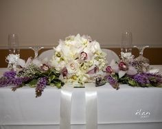 Head table centerpiece using Bride's bouquet and floral arrangements from cermony pew flowers.