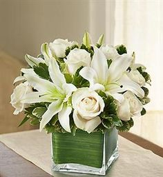 White flower arrangement with roses and orchids.