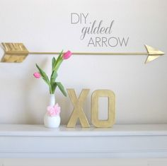 diy gilded arrow.  make this from a wooden dowel, cardstock and gold spray paint.