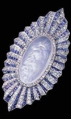 AN UNUSUAL ART DECO MOONSTONE, SAPPHIRE AND DIAMOND BROOCH, BY PAUL BRANDT, CIRCA 1920. Set with an oval-shaped carved moonstone depicting a reclining female figure and angel with a diamond-set border to the calibré-cut sapphire and diamond pleated surround, signed P. Brandt, numbered. #PaulBrandt #ArtDeco #brooch