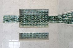 Double shower niche with decorative green glass accent tile