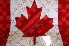 I teased you a while ago with pics of the fabrics for The Canada Quilt. And here it is… I didn't have anyone else to help hold it up, so its draped over the couch. Some friends of our…