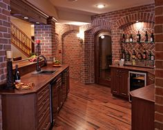 Double level Wooden Hammer solid walnut countertops. Custom recessed brick niches evoke a rustic charm. The beautiful brick archways that were built throughout this lower level along with  hickory flooring give an old world feel. Also, Wooden Hammer custom door leading to a brick wine cellar. By: M.J. Whelan Construction  pg.21