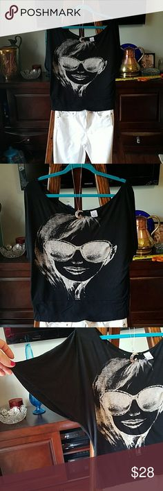 """Ladies Black n silver crop blouse Size M Absolutely one of the coolest shirts I've ever owned. my favorite! So comfy with 100% Rayon fabric. So chic with beauty in BLING rhinestone lined sunglasses with georgeous full lips in black/white monochromatic scale.  It's too small for me.. One small hole at neckline mended by me. No tag with maker..wish I could remember who made it..i would try to find another. off shoulder sleeve, wide scoop neck.  19"""" P to pit. 23.5"""" shldr. to hem. Waist 16.5""""…"""