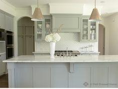 Dove blue cabinet color, arched doorways, herringbone pattern white tile backsplash, simple brass pendant lights, custom hood