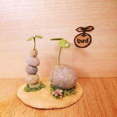 大きな石ころに負けじと小さな石ころが重なって背比べ。大きな双葉にはガラスの雫がついています。小さな花も咲いています。●素材 石粉粘土・水苔・ワイヤー ・ガラス...|ハンドメイド、手作り、手仕事品の通販・販売・購入ならCreema。