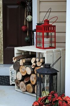 Christmas Porches... simple way to invite the season in using lanterns, a crate box with firewood and a poinsettia.