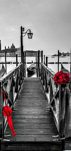 !!! Red Roses !!! romantic Venice. The main objects are colours red which is brighter and a different colour to the rest makes our eyes draw attention to those objects. Maybe a person set it up for someone and they've been left so red shows danger and upset.