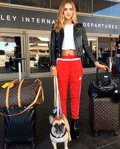 Street style look com cropped branca, calca vermelha esportiva e tênis.
