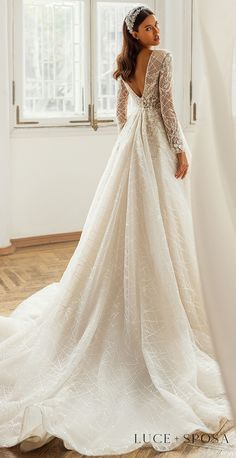 Glamorous Sparkly Long sleeves a-line wedding dress with Crystal Embellishments on lace bodice and deep v open back | Luce Sposa Wedding Dresses 2021- Kayley - Belle The Magazine #weddingdress #weddingdresses #bridalgown #bridal #bridalgowns #weddinggown #bridetobe #weddings #bride #dreamdress #bridalcollection #bridaldress #dress See more gorgeous bridal gowns by clicking on the photo