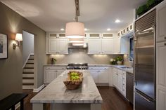 Cabinets that reach all the way to the ceiling allow for extra storage and give this small kitchen a grand feel. A mix of pendant, sconce and recessed lighting, high end appliances and a neutral ceramic tile backsplash complete the stylish space.
