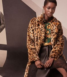 Oumie Jammeh models Zara faux fur leopard print coat, floral and polka dot print top and combined pleated skirt