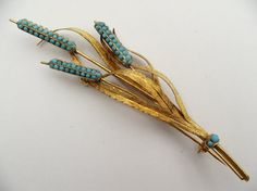 Gold brooch in the form of bunches of bulrushes with heads pavé-set with turquoise. ca. 1860 England.
