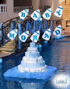 Big diaper cake in pool with balloons and tulle  for Baby Boy Blue Themed Baby Shower Decorations by Leila Events (01057). For orders or further info call or whatsapp +201222220889