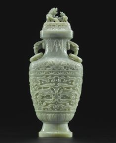 LARGE CELADON JADE VASE AND COVER QING DYNASTY, 19TH CENTURY of flattened baluster form, each side well-carved with floral arabesques forming a taotie mask, surmounted by a band of stylized lotus, the stone mottled with white and a russet inclusion |  Height 13 1/2  in., 34.3 cm. | Sotheby's