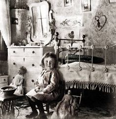 Girl in her room with her  dolls.