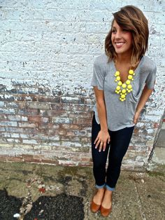 Super cute casual look: gray T with yellow necklace, dark wash skinnies, brown flats.