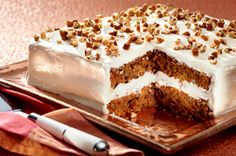 Shortcut Carrot Cake Recipe~ made with spice cake mix, pineapple, grated carrots and nuts. Frosting is delicious, light and fluffy cream cheese, confectioners sugar and Cool Whip!