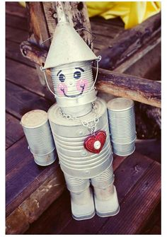 Tin Man Garden Decor.    Various cans + funnel + chain w/ heart.  Rustolium spray paint.  Add face detail.  Apply clear coat.  *something to weigh it down (maybe add it in the feet)