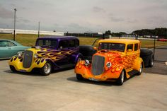 Two amazing flamed hot rods with matching trailers. The one on the left is a 1934 Chevrolet, and on the right. A 1934 Plymouth