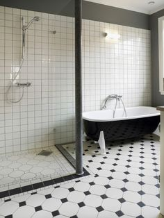 Likes: Cast-iron black and white tub Glass partitioned shower Shower fixtures  Dislike Checkered style tiles.