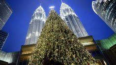 Un gran árbol de navidad emerge con la Torres Gemelas de Malasia de fondo