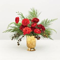 Classic Cheer Arrangement: Add ranunculus stems, mimicking the way flowers grow in nature by inserting some down low and placing some on top to create varying levels. Then tuck in a few carnations to fill in holes.